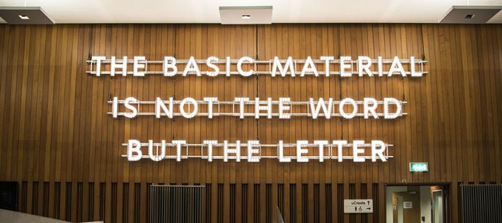 It reads: The Basic Material is not the Word but the Letter – also the name of the piece.