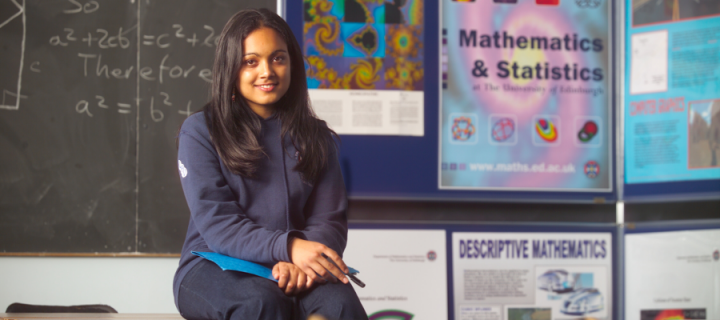 Female student sitting on desk in Maths classroom
