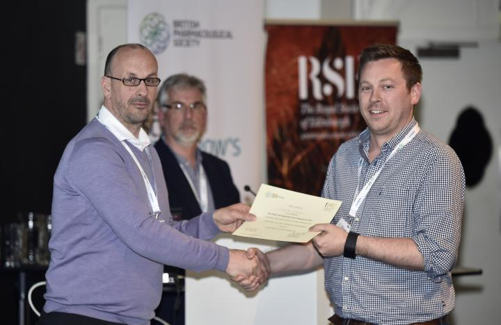 Douglas Gibson receiving a prize certificate from conference organisers