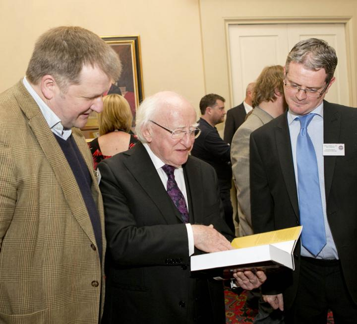 Photo showing President Higgins looking at a book presented to him by Professor Jackson.