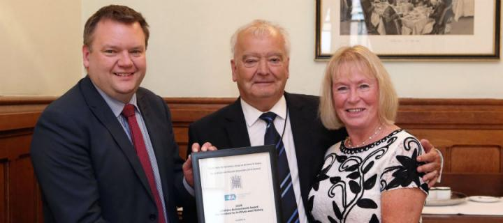 Sir Tom Devine receives his award from Nick Thomas-Symonds, MP alongside Catherine Devine