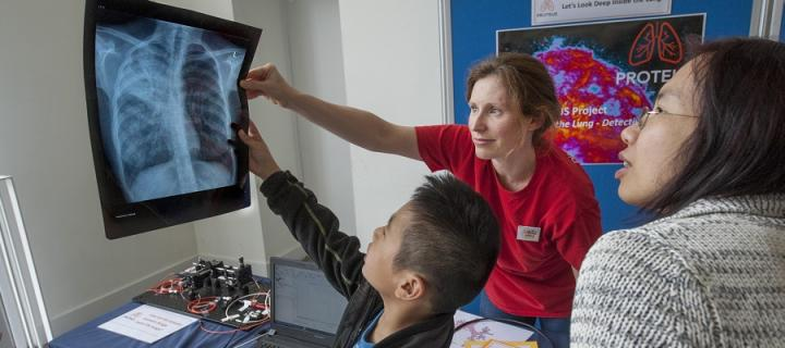 Researcher explains image to visitors at Edinburgh International Science Festival
