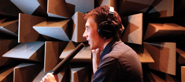 Man speaking into a mic in the University's near-anechoic chamber
