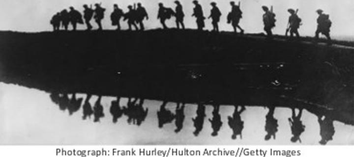 Soldiers walking along the horizon and reflected in the water