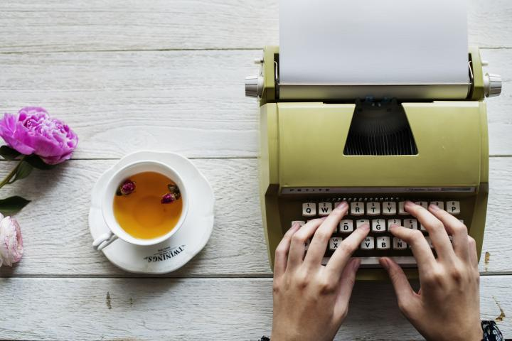 Someone typing on a typewriter, with a cup of tea beside them and some flowers.