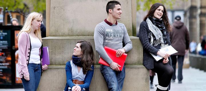 Photo of students under Adam Smith statue