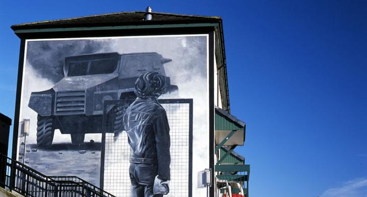 The Rioter mural - a gray painting on a building showing a rioter with a wire mesh shield facing an armoured car