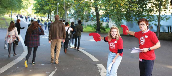 Students pointing along Middle Meadow Walk with large foam hands