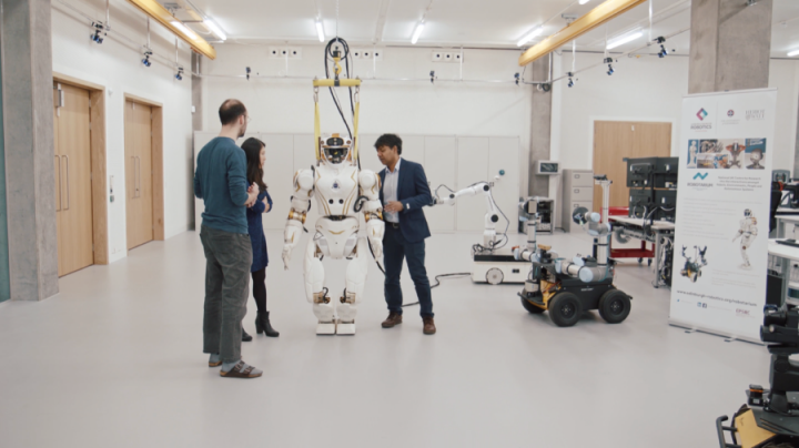 Three researchers working with the Valkyrie humanoid robot