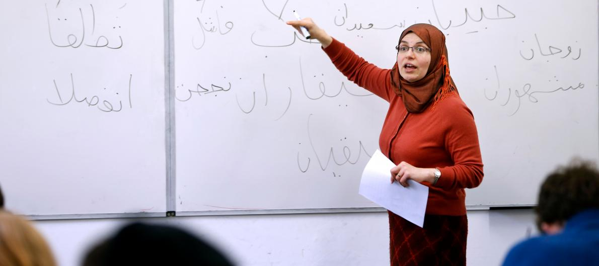 A lecturer presents to a class in front of a white board