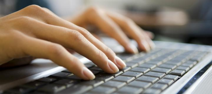 Woman's hands typing on a keyboard