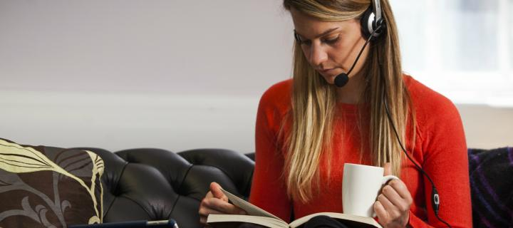 Online student wearing headset and studying book