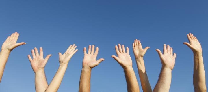 Hands raised into the blue sky