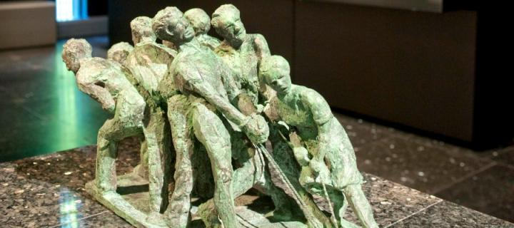 Green sculpture of a group of workers by Professor Rostowski