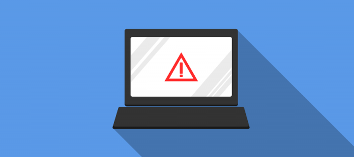 A laptop screen showing a warning symbol