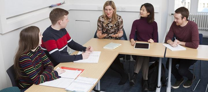 Four students sitting in a tutorial or seminar with a young female tutor