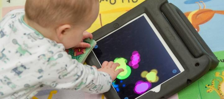 A baby interacts with a digital game on an ipad