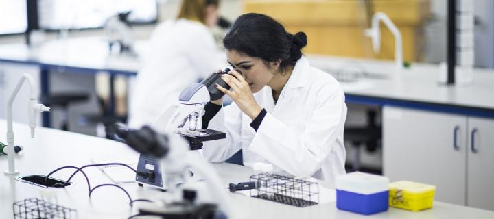Biomedical researcher with microscope