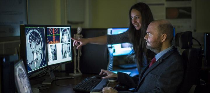 Two people looking at the human brain on two computer screens