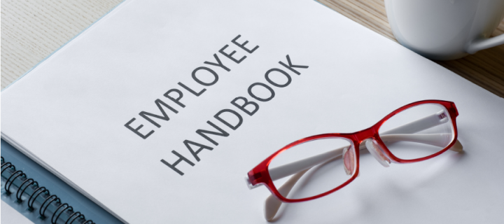 employee handbook with glasses on top