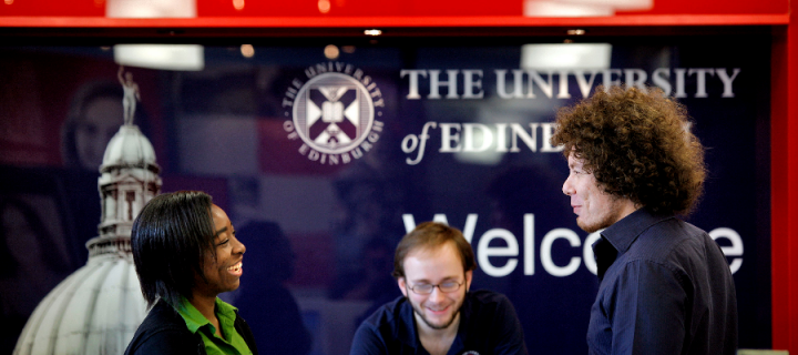 A woman and two men smiling and talking in front of a University of Edinburgh welcome sign