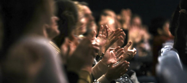Audience hands clapping in a dark auditorium