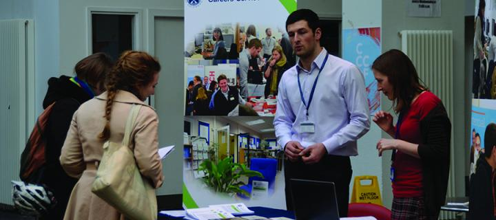 Two members of Careers Service staff talking to a female student at an information stand at a careers fair