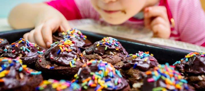 child picking out chocolate cakes from a tray