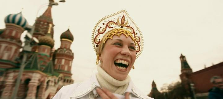 a woman in traditional Russian religious dress stands on Red Square laughing