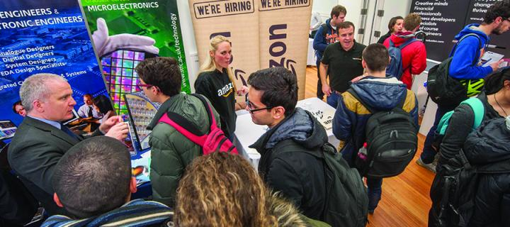 Several information stands at a careers fair in the Sanderson Building with students and employers