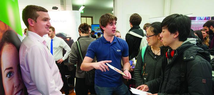 A male and female student talking to employer on an information stand at a careers fair