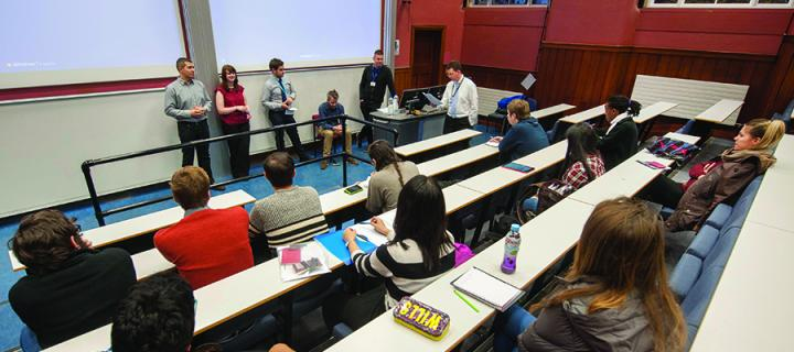 Students sitting in a lecture theatre with a group of employers standing at the front of the lecture theatre