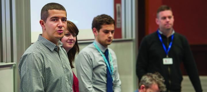 A group of employers standing at the front of a lecture theatre