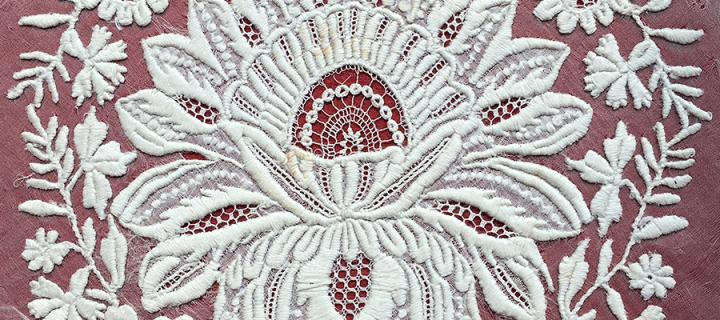 white embroidery of a flower on a white gauze background, mounted on red fabric