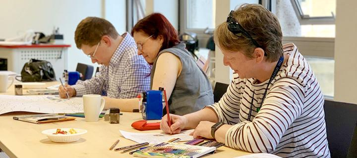 3 adults sitting at a desk creating new artworks with coloured pencils