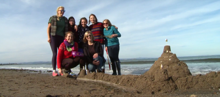 students stand next to a sandcastle they have built on a beach