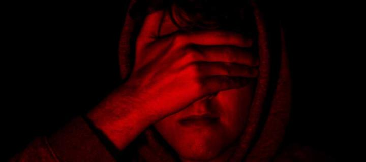 Red image of man with hand over face