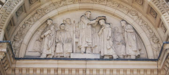 Carving of scholars in stonework of McEwan Hall exterior