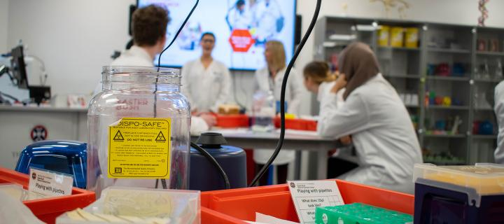 A PhD student teaches school pupils how to use lab techniques.