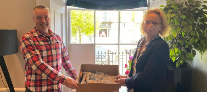 Streetwork's Rankin Barr receives a donation of face masks from Professor Natascha Gentz