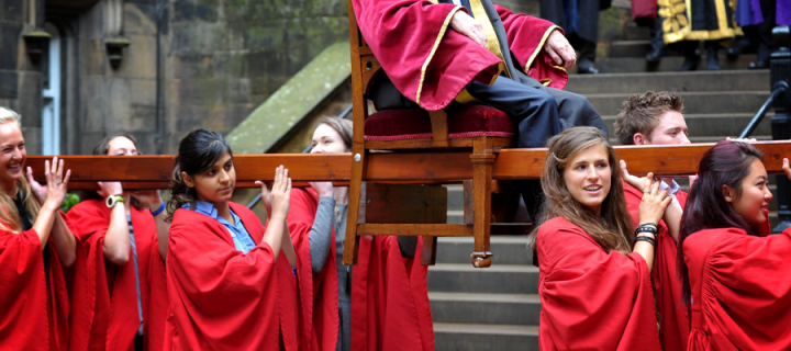 """Chairing"" of the Rector - 8 students in red roles with the Rector in a special seat resting on their collective shoulders"