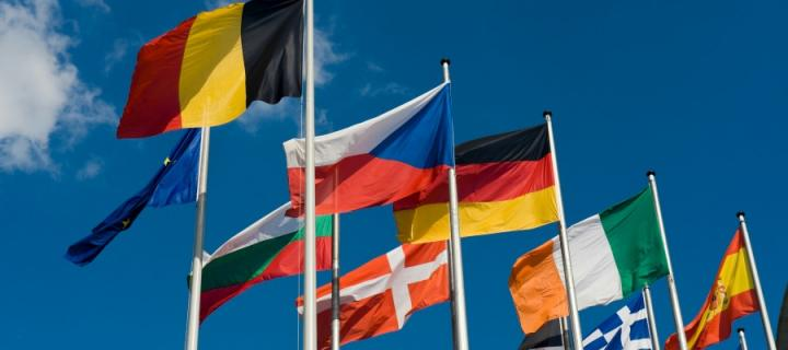 Flags of different European countries against a blue sky