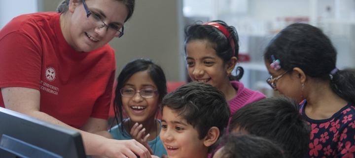 Children taking part in an activity with an Edinburgh University volunteer