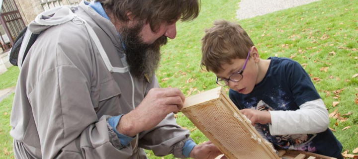 Scientist Dr Mark Barnett showing a young child the bee apiary