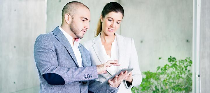 A man and a woman in business attire looking at an iPad
