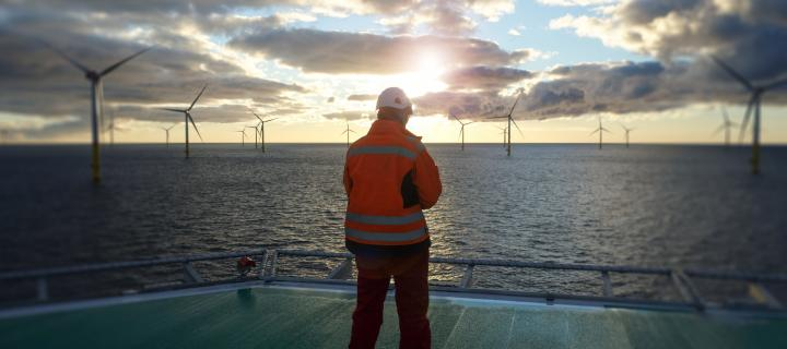 Offshore worker looking at wind turbines