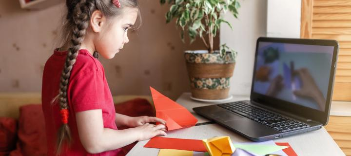 A young girl folds bright paper whilst looking at instructions on a laptop
