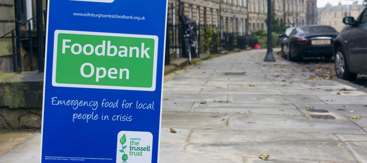 Bright blue sign outside of a grey stone building that says 'Food Bank Open'
