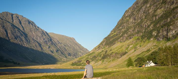 Man sitting on a rock on his own facing a loch in Glencoe