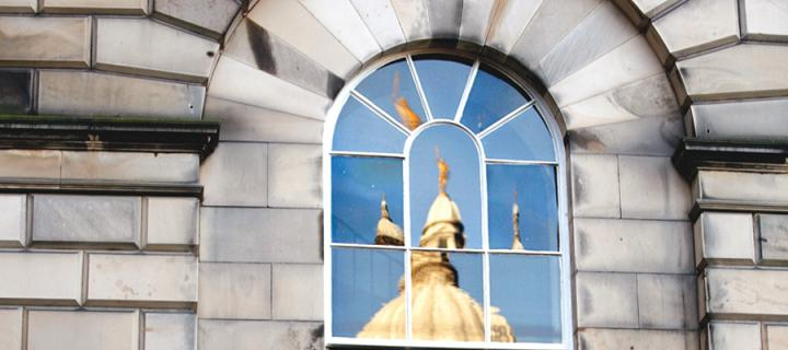 The 'golden boy' statue at Old College, reflected in the panes of a window